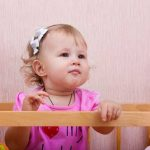 Dieťatko vylieza z postieľky