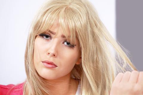 Blondinka, ktora ma problem s vlasmi. Nespokojny vyraz.