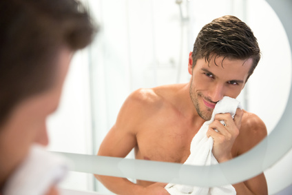Portrait of a man with towel looking at his reflection in the mirror in bathroom
